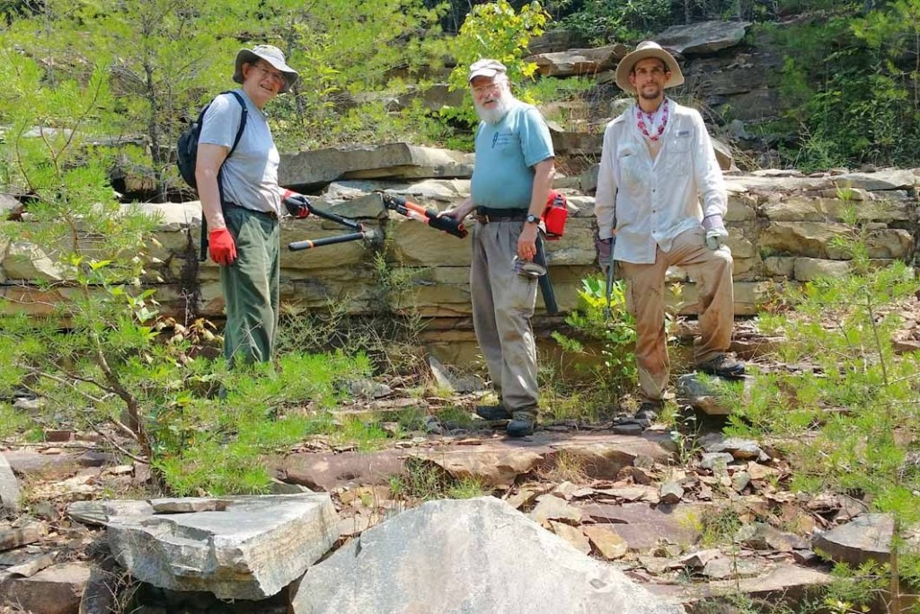 Volunteers take a moment to explore a long abandoned rock quarry in the cliffs high above Daddys Creek
