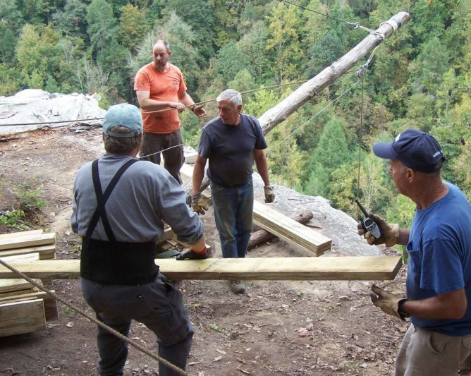 Tony Hook (in orange) works with volunteers to load lumber on the derrick for a 90 foot ride into Big Soddy Gorge during construction of the 100 foot suspension bridge, 2014. (Richie)