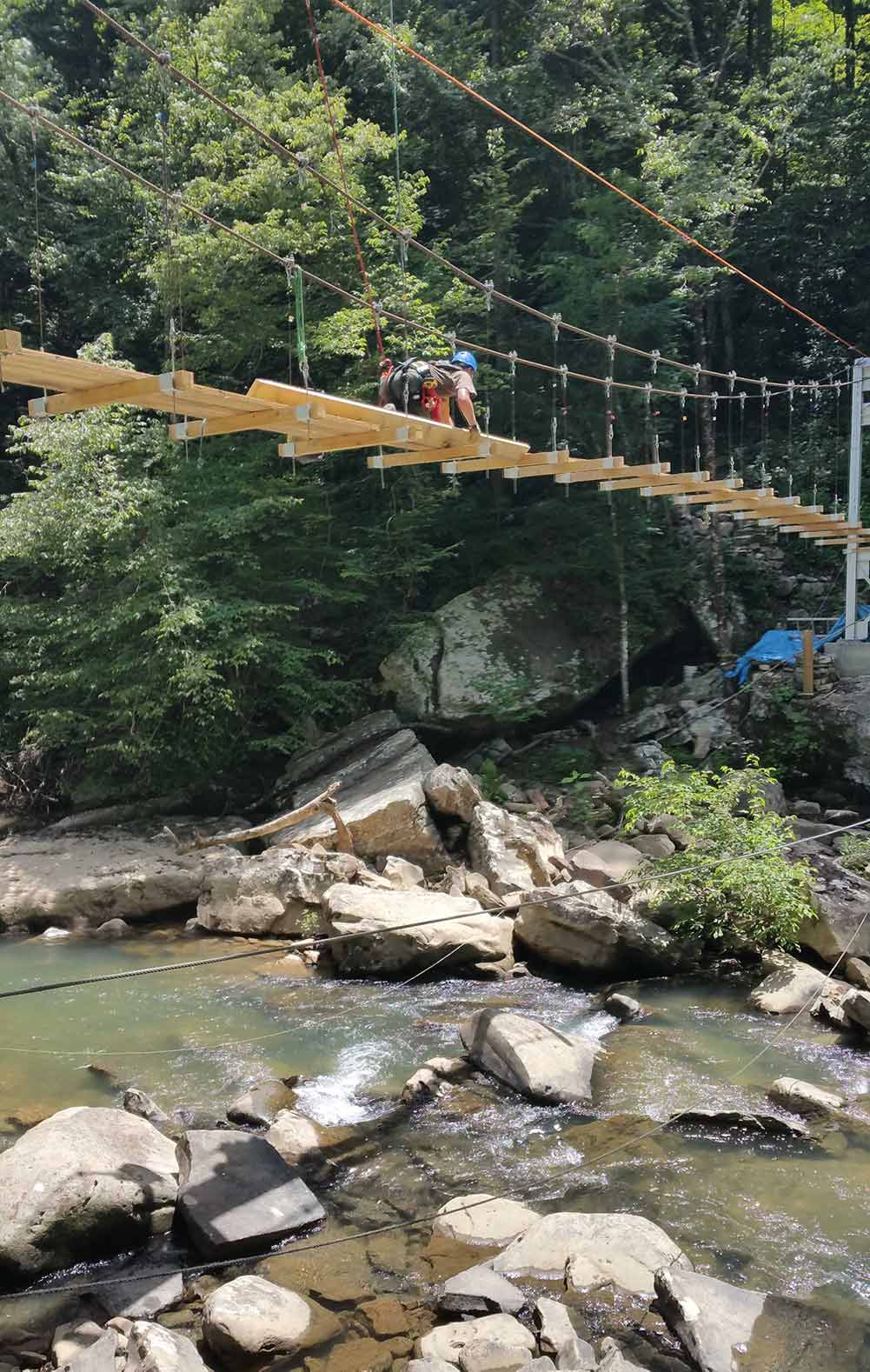 Tethered with a safety line, a worker secures treads to the Big Soddy Bridge during the summer of 2015
