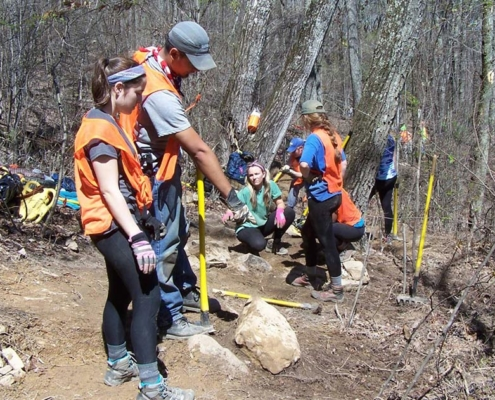 University of Delaware students engage in a little problem solving to build trail through a rocky area. (Richie)